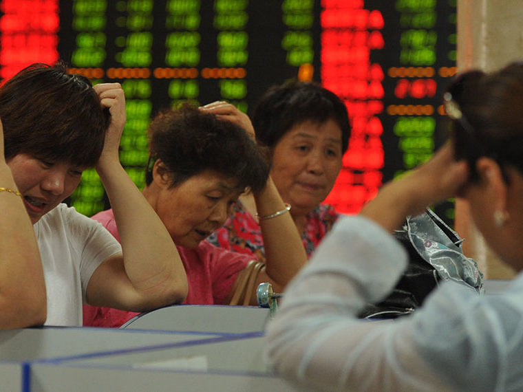 Women in front of a stock ticker board