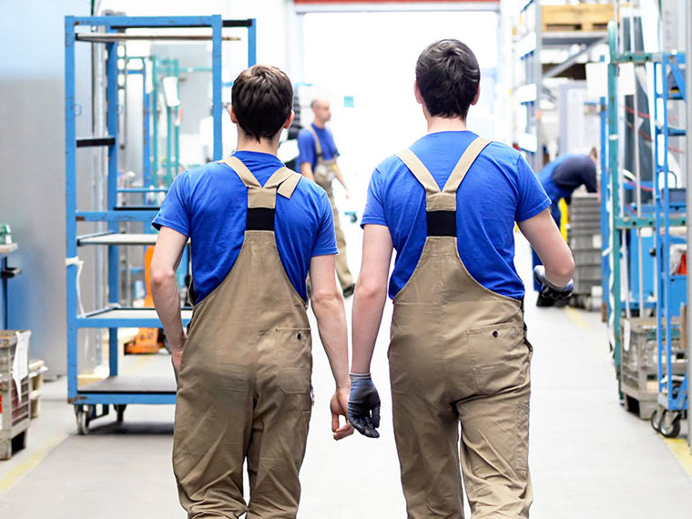 Two male workers walking in storage room