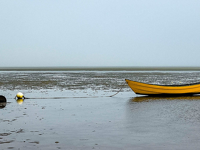 Row boat stranded on the beach at low tied