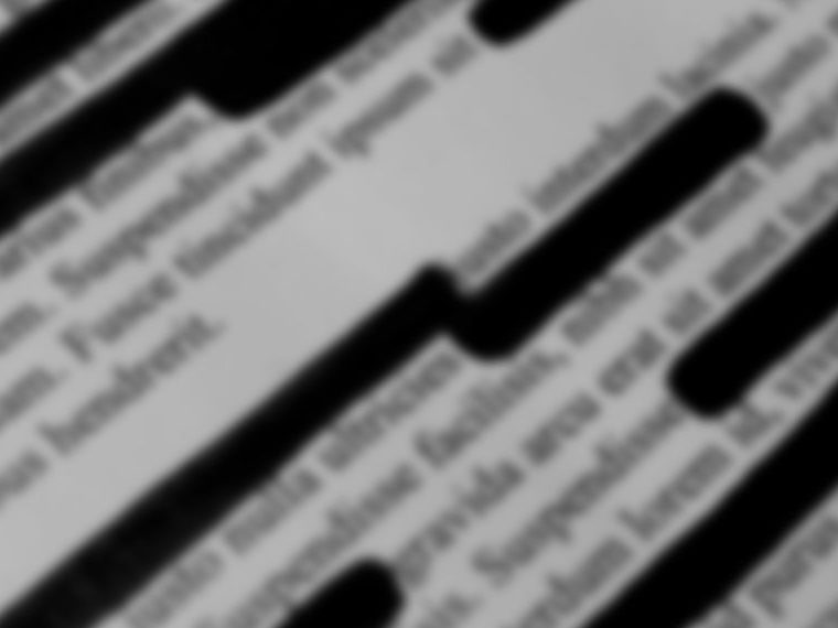 Blurry image of a document that has redaction