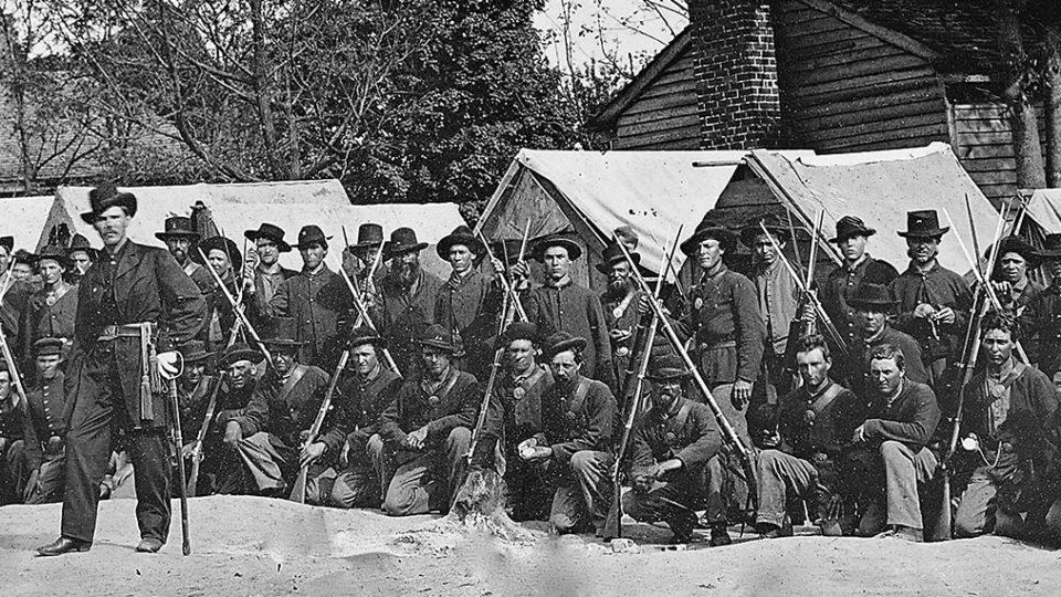Soliders kneeling behind 2 other soldiers in civil war era.