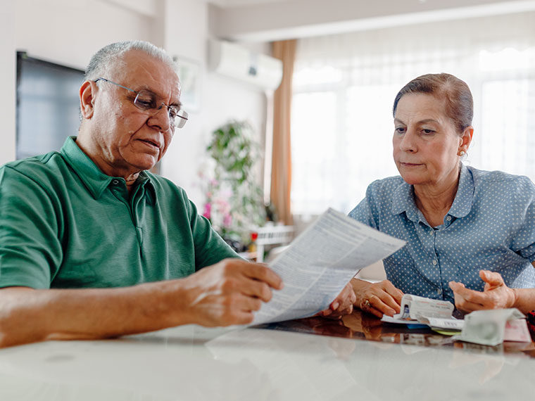 Elderly couple looking through paperwork and receipts