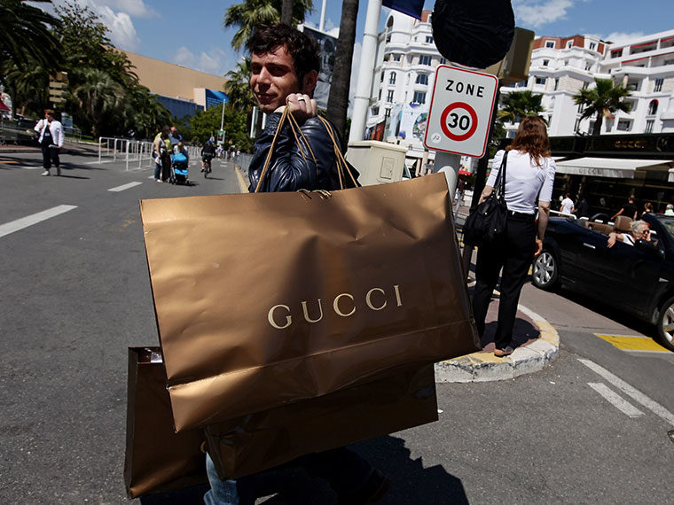 An individual is crossing the street and holding three Gucci shopping bags: two of the bags are held over the shoulder. They are looking slightly above the camera's angle.