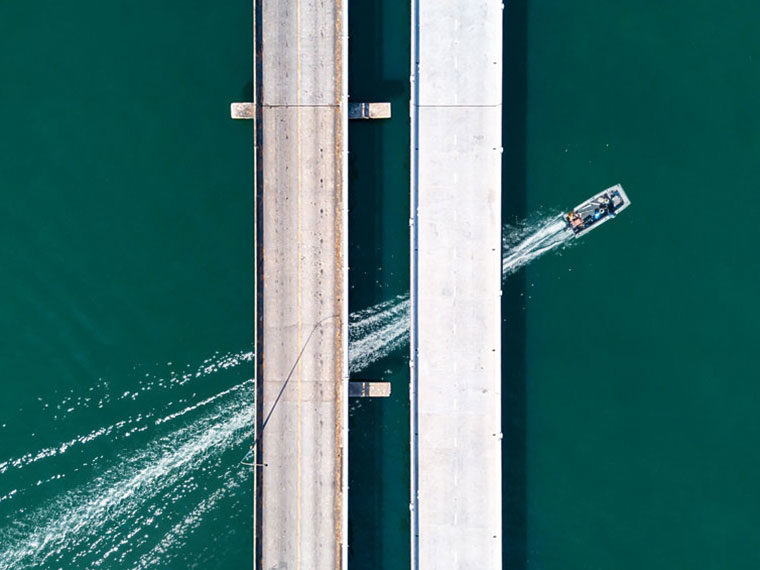 Aerial view of two bridges over water with a dinghy passing underneath