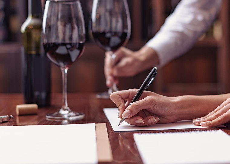 A hand preparing to write something on a black piece of paper. Two wine glasses sit on the table next to the hand