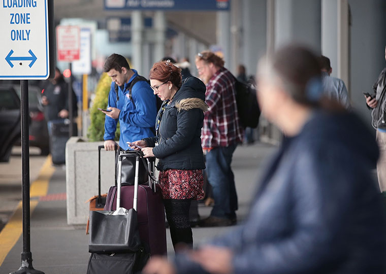 An image of several people looking down at their phones while they wait outside at an airport pick-up and drop-off loading zone