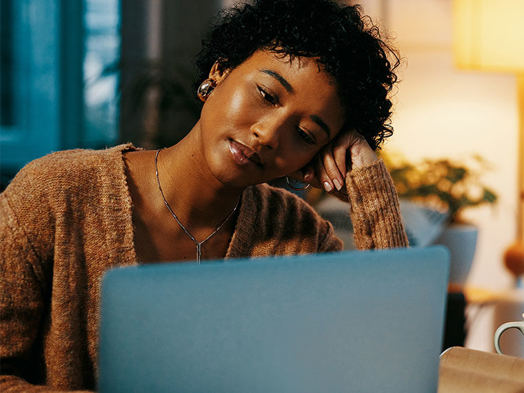 An individual sits with their head resting on their hand while they look at their computer