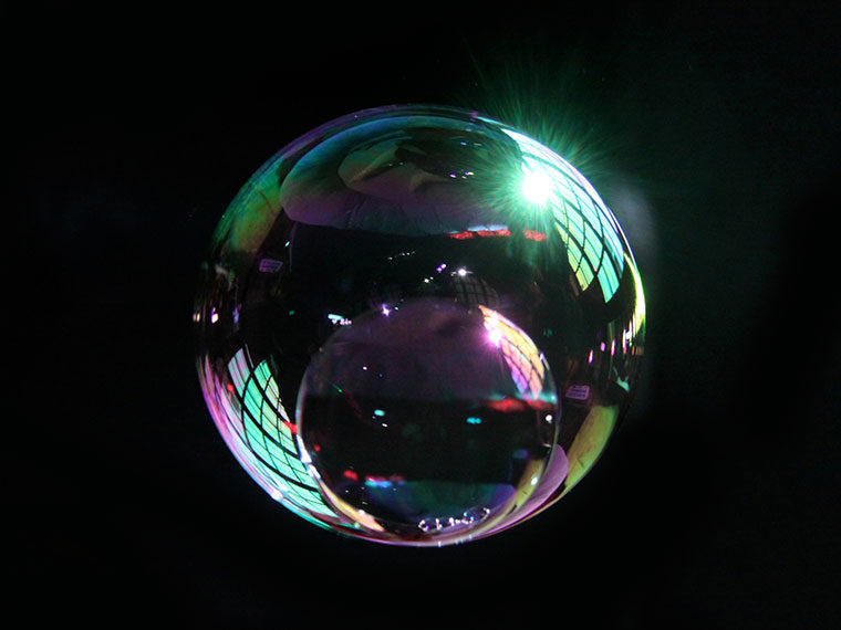 A bubble refracts light and the image of a window