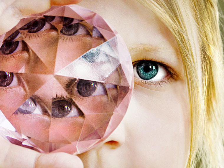 Person looking through a multifaceted gemstone
